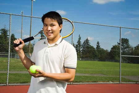 playing tennis: A young sporty asian man playing tennis Stock Photo