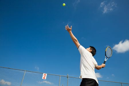 toss: A sporty young asian male playing tennis
