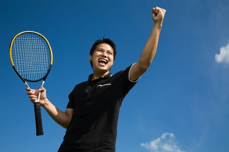 A young sporty asian tennis player screaming in joy of victory photo
