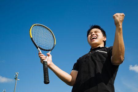 Een jonge sportieve Aziatische tennisser schreeuwen in de vreugde van de overwinning