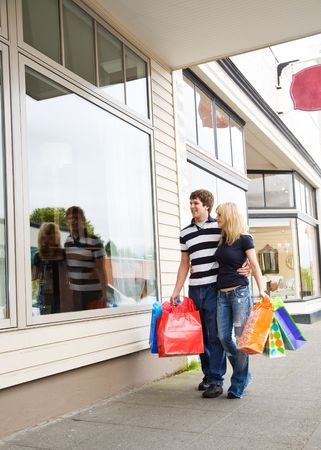 shop window: A caucasian couple carrying shopping bags on a shopping trip  Stock Photo