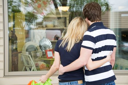 A young shopping caucasian couple looking into a store photo