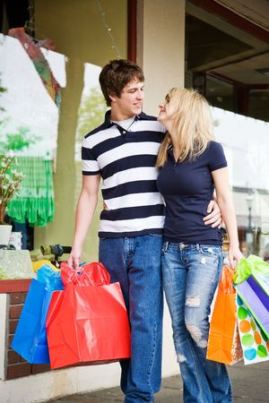 A caucasian couple carrying shopping bags walking in an outdoor mall Stock Photo - 3775564