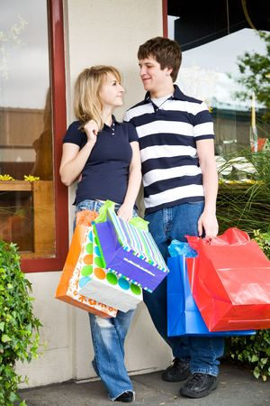 A caucasian couple carrying shopping bags in an outdoor mall photo