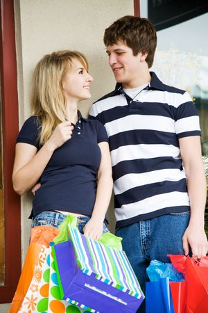 A young caucasian couple carrying shopping bags at an outdoor mall photo