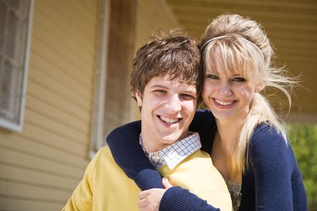 A portrait of a happy young caucasian couple in front of their house photo