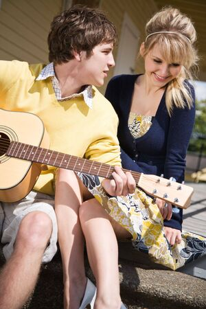 shy girl: A young caucasian man playing guitar and sings to his girlfriend Stock Photo