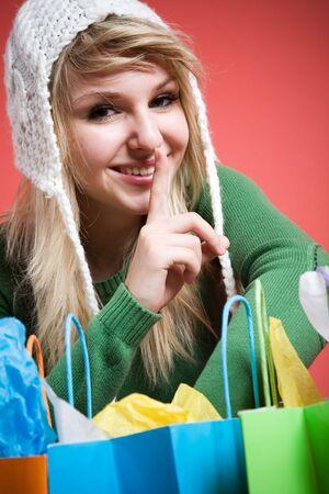 A beautiful caucasian girl shushing before opening shopping bags