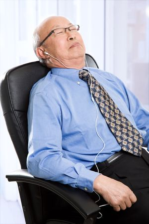 tired businessman: A senior asian businessman sleeping and listening to music at the office