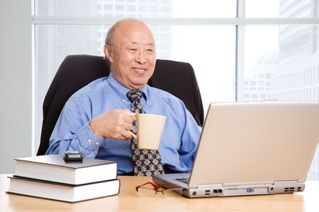 A senior asian businessman working in the office Stock Photo