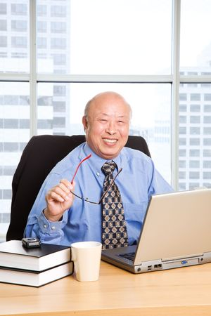A senior asian businessman working in the office photo