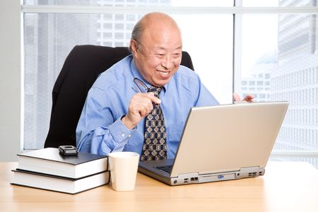 A happy senior asian businessman working in the office photo