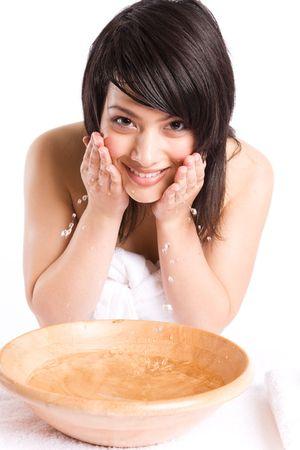 A beautiful asian girl washing face at a spa photo