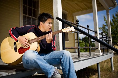 A young asian male playing guitar outside  Stock Photo