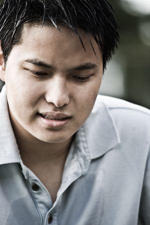 A portrait of a sad young asian male photo