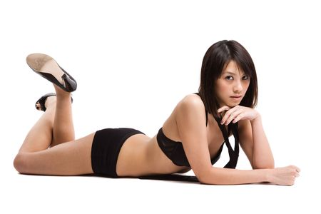 An isolated shot of a beautiful sexy asian girl in lingerie lying down on the floor photo