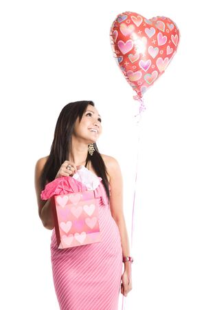 A beautiful asian woman carrying a heart-shaped balloon and valentine gifts photo