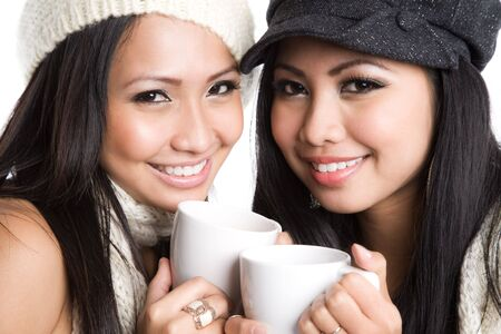 Two beautiful asian women drinking coffee