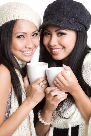 Two beautiful smiling asian women drinking coffee