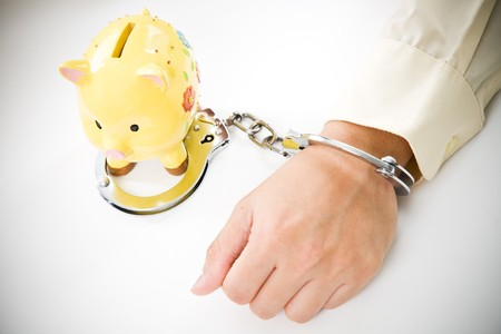 A conceptual shot of a businessman tied up with handcuffs to a piggy bank, can be used to represent financial trouble concept photo