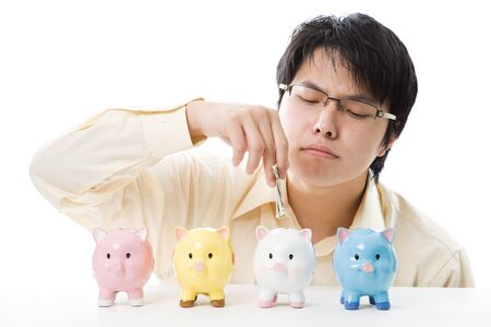 An isolated shot of an asian businessman saving money into piggy banks photo