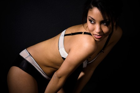 A beautiful sexy african american woman wearing lingerie shot in black background