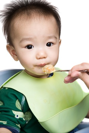 A shot of an asian baby during feeding time photo