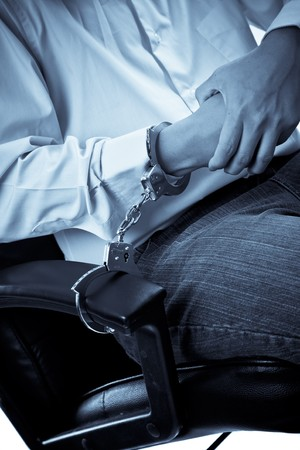A conceptual shot of a businessman being handcuffed to an office chair photo