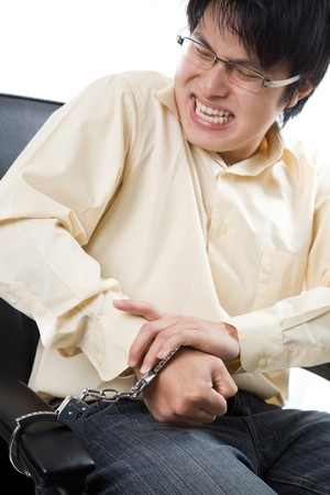 A conceptual shot of an asian businessman being handcuffed to an office chair Stock Photo - 4259034