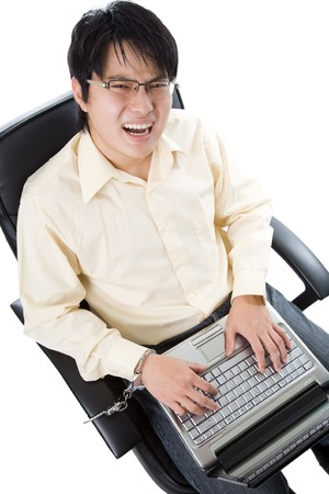 A shot of a businessman handcuffed on a chair working on his laptop photo