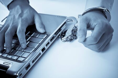 A shot of a businessman handcuffed on laptop Stock Photo - 4267119