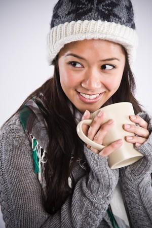 A shot of a happy beautiful asian woman drinking coffee photo