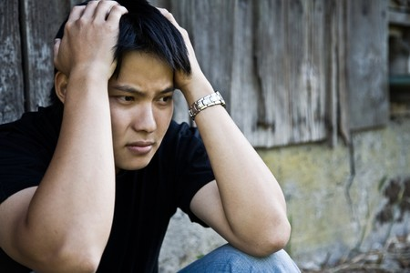 depressed person: A shot of a stressed asian male outdoor