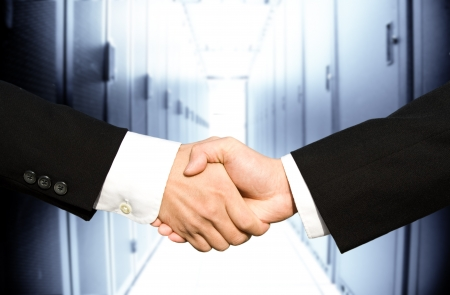 Two businessmen shaking hands in a technology data center Stock Photo