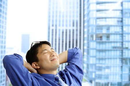 A shot of an asian businessman resting at the office Stock Photo - 4325480