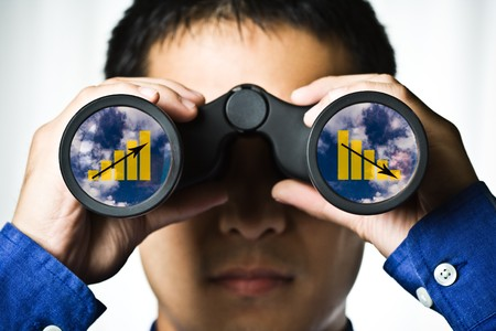 future earnings: A businessman looking through binoculars, seeing conflicting trends in earnings prediction, can be used for business vision or business prediction concept