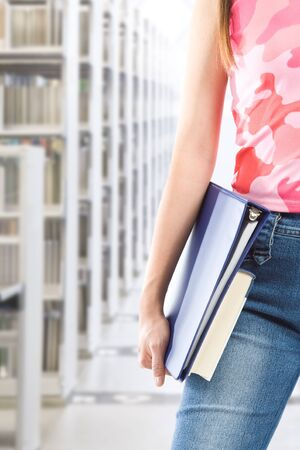 A shot of a student carrying books at the library photo