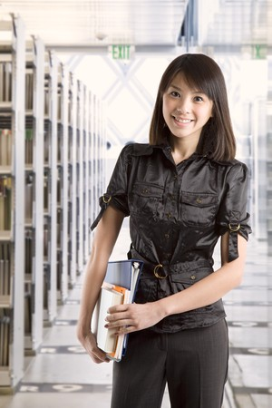 An asian college student carrying books at the library photo