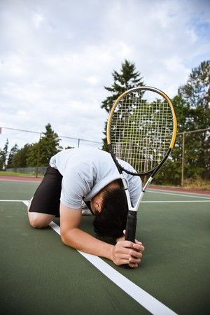 defeated: A sad asian tennis player kneeling down in disappointment after defeat