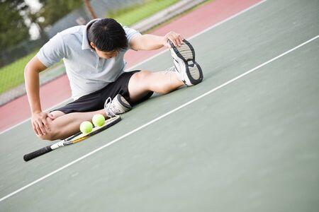 Een Aziatische mannelijke tennisser strekt voor het afspelen