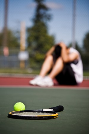 defeat: A sad male tennis player sitting down in disappointment after defeat