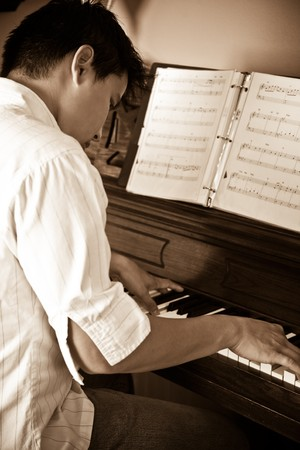 sled: A shot of an asian man playing piano