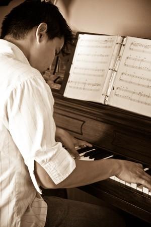 tocando el piano: Una foto de un hombre tocando el piano asi�tico Foto de archivo