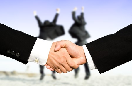negotiation business: Two businessmen shaking hands with other two businessmen celebrating in the background, can be used for success concept