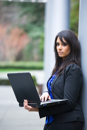 working: A shot of an indian businesswoman working on her laptop outdoor