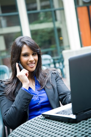 A shot of an indian businesswoman talking on the phone and working on her laptop outdoor photo