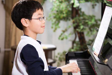 아시아 소년 재생 피아노의 총