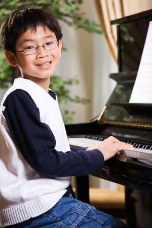 A shot of an asian boy playing piano