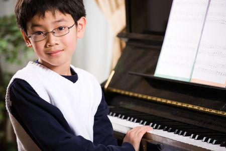 playing instrument: A shot of an asian boy playing piano