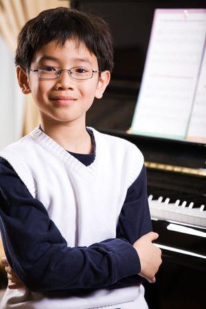 tocando el piano: Una foto de un ni�o asi�tico tocando el piano